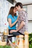Młody kochający mężczyzna i dziewczyna ma flirtu przy domową kuchnią Zdjęcie Stock