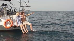 Młody kochający pary obsiadanie na karmie żagiel łódź, myje iść na piechotę w wodzie morskiej zbiory