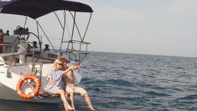 Młody kochający pary obsiadanie na karmie żagiel łódź, myje iść na piechotę w wodzie morskiej zbiory wideo