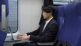 Młody Koreański biznesmen pracuje z laptopu obsiadaniem w chodzenie pociągu zbiory