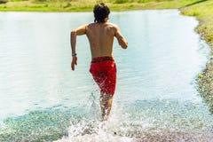 Młody koreański mężczyzna biega jego plecy na wodzie z uśmiechem i nagą półpostacią Obraz Stock