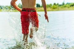 Młody koreański mężczyzna biega jego plecy na wodzie z uśmiechem i nagą półpostacią Obrazy Stock