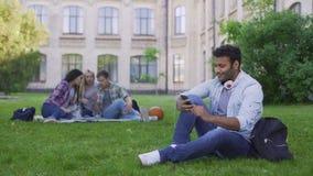 Młody Latynoski męskiego ucznia obsiadanie na trawie i scrolling na telefonie komórkowym, relaksujemy zbiory wideo