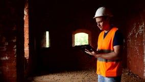 Młody męski architekt egzamininuje starego ściennego budynek, odbudowa zdjęcie wideo