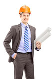 Młody męski architekt jest ubranym hełm i trzyma projekty Fotografia Stock