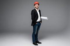Młody męski architekt jest ubranym hełm i trzyma projekty Zdjęcia Royalty Free