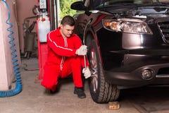 Młody męski auto mechanika śrubowanie lub odśrubowania samochodowy koło wre Fotografia Royalty Free