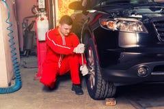 Młody męski auto mechanika obsiadanie blisko czarnego śrubowania i sedanu Zdjęcia Royalty Free