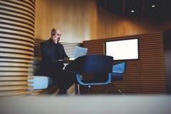 Młody męski bankowiec jest siedzącym pobliskim ekranem z egzaminem próbnym up Fotografia Royalty Free