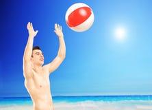Młody męski bawić się z plażową piłką obok morza, Obrazy Royalty Free