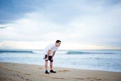 Młody męski biegacz ubierał w białej koszulka odpoczynku pozyci na plaży na pięknym dennym tle Obrazy Stock
