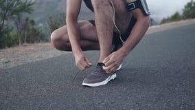 Młody męski biegacz wiąże shoelaces zbiory wideo