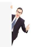 Młody męski biznesmen daje kciukowi up, stojący za pustego miejsca pa Obraz Royalty Free