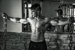 Młody męski bodybuilder w gym pozuje z metali łańcuchami Fotografia Stock