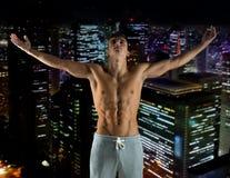 Młody męski bodybuilder z nastroszonymi rękami Fotografia Stock