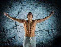 Młody męski bodybuilder z nastroszonymi rękami Obrazy Stock