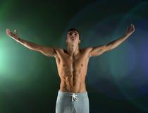 Młody męski bodybuilder z nastroszonymi rękami Zdjęcia Royalty Free