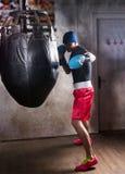 Młody męski bokser trenuje z boksu uderzać pięścią w bokserskich rękawiczkach Zdjęcia Royalty Free