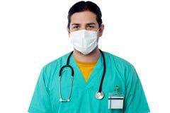 Młody męski chirurg jest ubranym twarzy maskę Obraz Stock