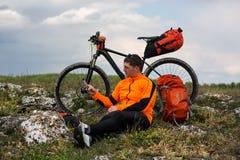 Młody Męski cyklista Opowiada Na telefonie komórkowym Obrazy Stock