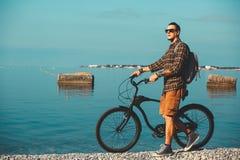 Młody Męski cyklista Z Rowerowym odprowadzeniem Na Brzegowym I Cieszy się widoku morze Wakacyjny podróży aktywności pojęcie Zdjęcia Royalty Free
