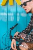 Młody Męski cyklisty obsiadanie Na Rowerowego Pobliskiego błękit ściany tła Dziennego stylu życia Miastowym Odpoczynkowym pojęciu Zdjęcia Stock