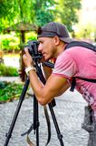 Młody męski fotograf fotografuje naturę w parku na bl fotografia stock