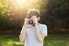 Młody męski fotograf robi fotografiom z rocznik kamerą podczas gdy stojący przy zieloną trawą Fachowa samiec używa retro kamera f Fotografia Stock