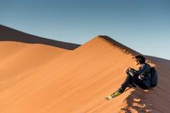 Młody męski fotografa obsiadanie na piasek diunie, Namibia Fotografia Royalty Free