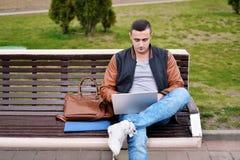 Młody męski freelancer pracuje z laptopem w ulicie na ławce fotografia stock
