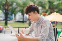 Młody męski freelancer używa cyfrową pastylkę w wygodnej kawie Zdjęcia Stock