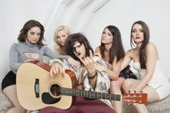 Młody męski gitarzysta z chłodno gestem otaczającym żeńskimi przyjaciółmi Obrazy Royalty Free