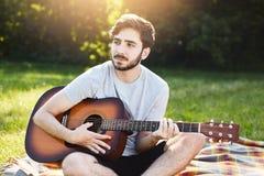 Młody męski gitarzysta z modną fryzurą, ciemnymi oczami i gęstą brodą bawić się gitarę przy zmierzchu obsiadaniem krzyżującym, iś Zdjęcia Royalty Free