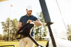 Młody męski golfista patrzeje wristwatch Obraz Stock