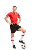 Młody męski gracz futbolu kroczy nad piłką Zdjęcia Royalty Free
