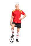 Młody męski gracz piłki nożnej stoi nad piłką Zdjęcie Stock