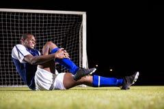 Młody męski gracza piłki nożnej cierpienie od kolano bólu na placu zabaw Zdjęcie Stock