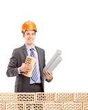 Młody męski inżynier trzyma cegłę i projekt za cegłą Obraz Stock