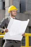 Młody męski inżyniera mienia projekt podczas gdy patrzejący daleko od przy budową Obraz Royalty Free