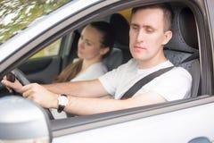 Młody męski kierowca patrzeje bocznego widoku lustra Zdjęcie Royalty Free