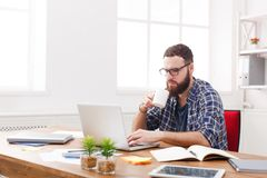 Młody męski kierownik w szkła działaniu z laptopem w nowożytnym białym biurze Obraz Stock