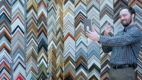 Młody męski klient bierze selfie z cyfrową pastylką w ramowym atelier Zdjęcie Stock