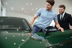 Młody męski klient dostaje wśrodku jego nowego samochodu Zdjęcie Royalty Free