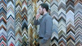 Młody męski klient patrzeje dla ramy dla jego obrazka w atelier Fotografia Stock