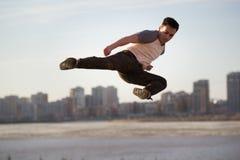 Młody męski kopnięcie wojownik wykonuje akrobatycznego kopnięcie przed linią horyzontu Fotografia Stock