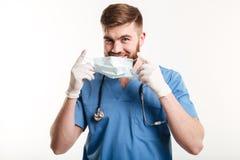 Młody męski lekarz medycyny lub pielęgniarka stawia bezpłodną maskę Obraz Stock
