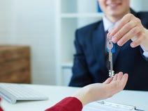 Młody męski makler daje kluczom nowy dom żeński klient Fotografia Stock