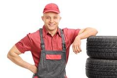 Młody męski mechanik opiera na wiązce opony Zdjęcie Stock