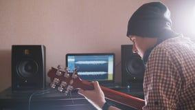 Młody męski muzyk komponuje ścieżkę dźwiękowa bawić się gitarę i nagrywa używać komputer, hełmofony i klawiaturę, obraz stock