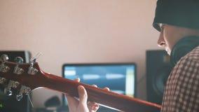 Młody męski muzyk komponuje ścieżkę dźwiękowa bawić się gitarę i nagrywa używać komputer, hełmofony i klawiaturę, zdjęcia stock